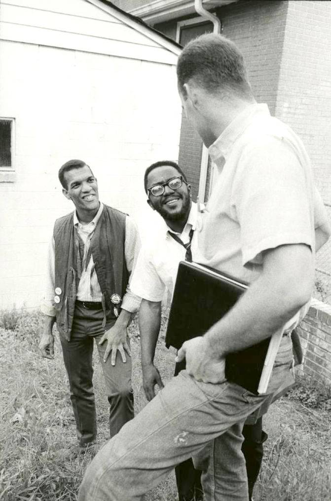 Three men standing on steps talking and smiling.